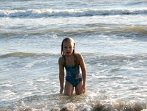 Little girl playing in the waves. At sea on a sunny day Stock Photos