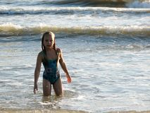Little girl playing in the waves. At sea on a sunny day Royalty Free Stock Image