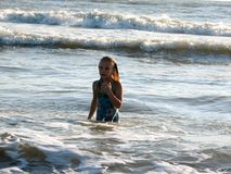 Little girl playing in the waves. At sea on a sunny day Stock Image