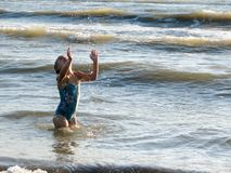 Little girl playing in the waves. At sea on a sunny day Stock Photography