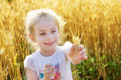 Little girl playing in the wheat field Royalty Free Stock Photo