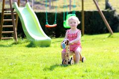 Little girl playing with wheel horse in the garden Royalty Free Stock Photography