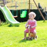 Little girl playing with wheel horse in the garden Stock Photo
