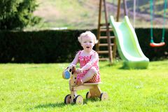 Little girl playing with wheel horse in the garden Royalty Free Stock Photos