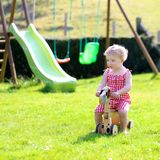 Little girl playing with wheel horse in the garden Royalty Free Stock Image