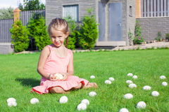 Little girl playing with white Easter eggs in the Stock Photos