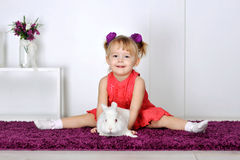Little girl playing with white rabbit Royalty Free Stock Image
