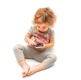 Little girl playing with white smartphone Royalty Free Stock Photos