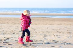 Little girl playing on winter beach Stock Photography