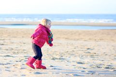 Little girl playing on winter beach Stock Photo