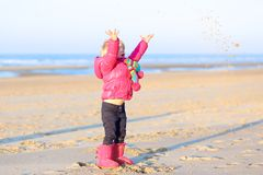 Little girl playing on winter beach Royalty Free Stock Photography