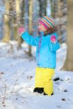 Little girl playing in winter forest Royalty Free Stock Photo