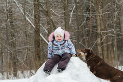 Little girl playing in winter forest on snowy hill Royalty Free Stock Photos