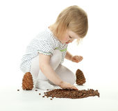 Little Girl Playing With Cedar Cones Stock Image