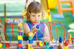 Little Girl Playing With Labyrinth Educational Toy. Royalty Free Stock Photo