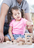 Little girl playing with wooden blocks against father in house Royalty Free Stock Images
