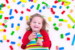 Little girl playing with wooden blocks Royalty Free Stock Photos