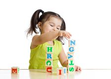 Little girl playing with wooden blocks with Stock Images