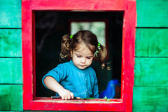 Little girl playing in wooden house in nature Stock Photo