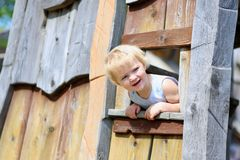 Little girl playing in wooden house in the park Royalty Free Stock Photo