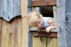 Little girl playing in wooden house in the park Royalty Free Stock Images