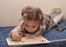 Little girl playing with wooden puzzle Royalty Free Stock Photo