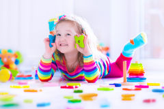 Little girl playing with wooden toy blocks Royalty Free Stock Photos