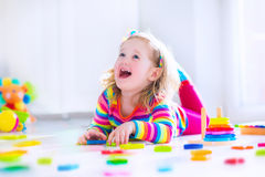 Little girl playing with wooden toys Royalty Free Stock Images