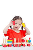 Little girl playing with wooden train toy Stock Photography
