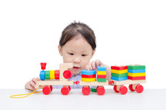 Little girl playing with wooden train toy Royalty Free Stock Images