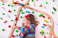 Little girl playing with wooden trains Royalty Free Stock Images