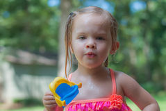 Little Girl Playing in the Yard. Little Girl Wearing Pink Bathing Suit Playing in the Yard Royalty Free Stock Image
