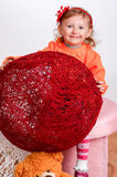 Little girl playing with yarn balls on a white background royalty free stock images