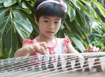 Little girl playing zither Stock Photo