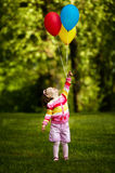 Little girl plays with balloons in park Royalty Free Stock Images