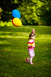 Little girl plays with balloons in park Stock Images