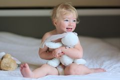 Little girl plays in bed with teddy bear Stock Photos