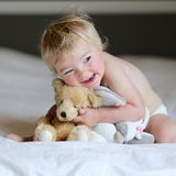 Little girl plays in bed with teddy bear Stock Image