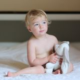 Little girl plays in bed with teddy bear Royalty Free Stock Photos
