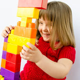 Little girl plays with blocks. Closeup of adorable three year old girl examining the tower she has just built with plastic blocks Stock Images