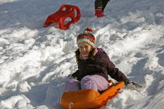 Little girl plays with bob on the snow Royalty Free Stock Image