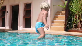 little girl plays on bottom of pool and scrambles out