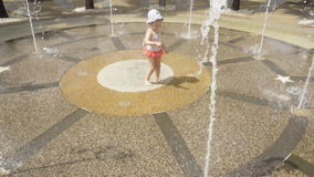 Little girl plays in the center of fountain stock video footage