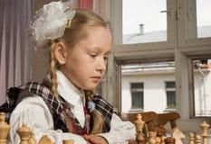 Little girl plays chess Stock Photos