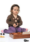 Little girl plays chess pieces Royalty Free Stock Photography