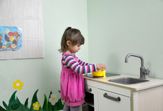 The little girl plays in children's kitchen Royalty Free Stock Photo
