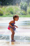 Little girl plays in city fountain. A laughing little girl things this water in the city fountain tickles Royalty Free Stock Photography