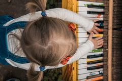 Little girl plays the color piano. Children& x27;s hands. Piano keys stock images