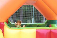 Little girl plays in colored air trampoline Royalty Free Stock Image