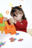 Little girl plays a colorful cubes Royalty Free Stock Image